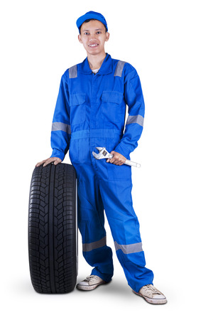 Portrait of friendly young technician with a blue uniform holding a black tire and wrench Stock Photo