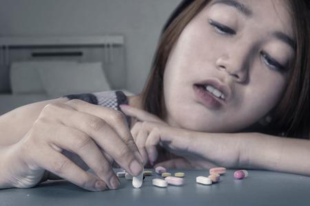 sobredosis: Retrato de joven muchacha asiática droga adicto y la elección de las píldoras en forma de narcóticos utilizados por ella misma Foto de archivo