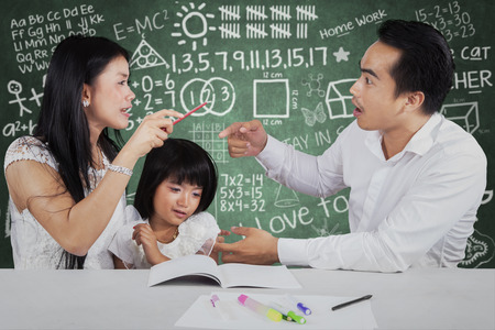 Portrait of little girl crying while her parents quarreling when help their child to study photo