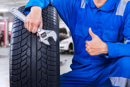automobile workshop: Technician with a blue workwear, holding a wrench and a tire while showing thumb up