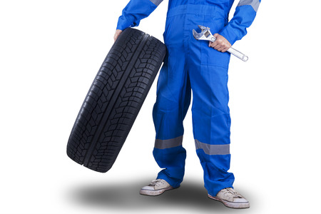 maintenance: Closeup of mechanic person with a blue uniform holding a wrench and a tire Stock Photo