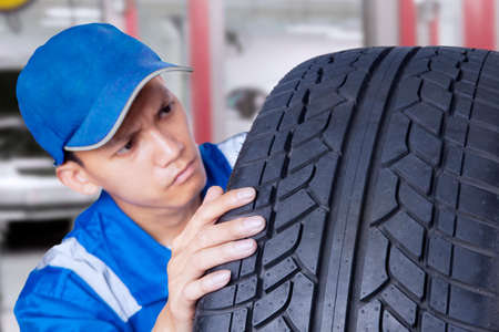 automobile workshop: Asian mechanic with a blue hat holding and checking a black tire in the workshop
