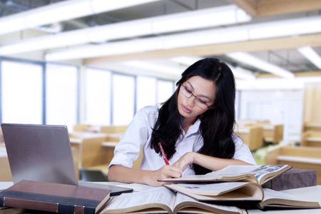 hispanic students: Portrait of young nerdy student studying with textbooks and write quotations on a book in the class Stock Photo