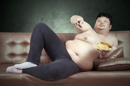 couch: Fat man eats fast food while watching tv at home