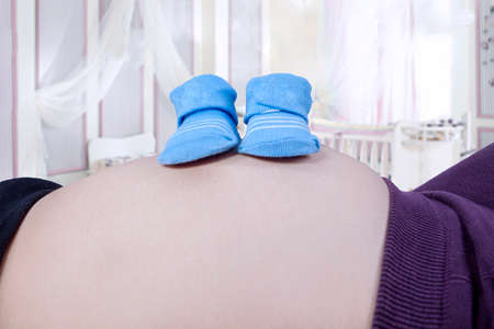 Blue baby shoes on the pregnant woman belly in the bedroom photo