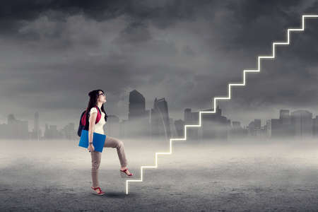 achieve goal: College student stepping up on stairs to gain her success