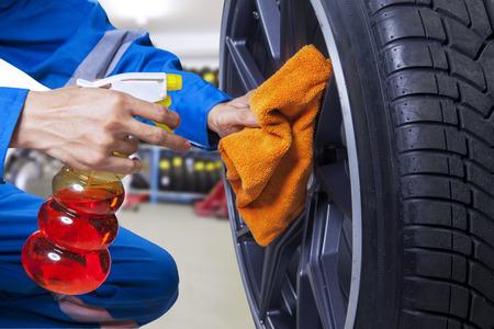 헝겊으로 먼지를 청소하여 타이어 테두리에 돌보는 정비사 손 확대 사진 스톡 콘텐츠