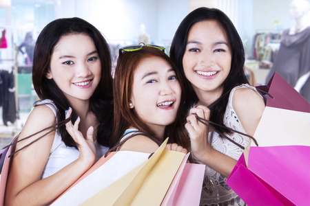 carrying girl: Group of happy teenage girls with shopping bags smiling at the camera in the mall