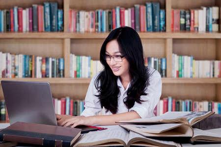 library: Retrato de estudiante inteligente que estudia en la biblioteca y el uso de un ordenador port�til