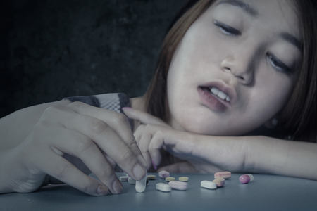 abuse young woman: Portrait of young girl addicted drugs, using narcotic shaped pills at home Stock Photo