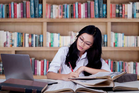 female student: Teenage girl studying with textbooks while writing on a book in the library Stock Photo