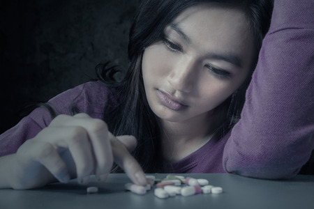 substance: Portrait of teenge girl choosing pills with stressful expression, symbolizing a drugs addict Stock Photo