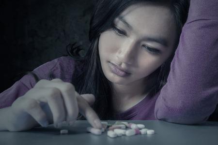 drogadiccion: Retrato de ni�a teenge elegir p�ldoras con expresi�n estresante, que simboliza un adicto a las drogas