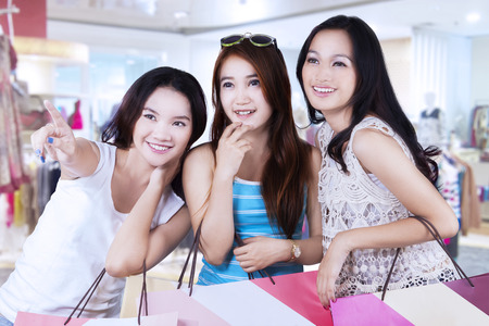 Portrait of teenage girl pointing a store with her friends in the shopping center
