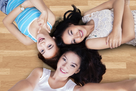woman looking: Unique perspective of three teenage girls lying down on the wooden floor and taking self photo together