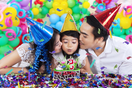 kids birthday party: Portrait of two parents kissing their daughter while blowing a birthday candle at home Stock Photo