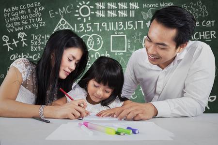 Niños ayudando: Retrato de colegiala feliz aprender a escribir con sus padres, againts tiro garabatear fondo