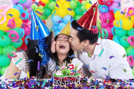 Enthousiaste petite fille célébrer sa fête d'anniversaire avec ses parents et obtenir baiser