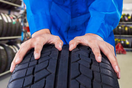 garage automobile: Gros plan des mains mécaniques avec uniforme bleu poussant un pneu noir dans l'atelier