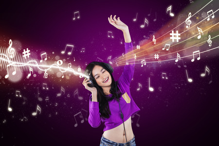Portrait of teenage girl singing and dancing while listening music with headphones photo