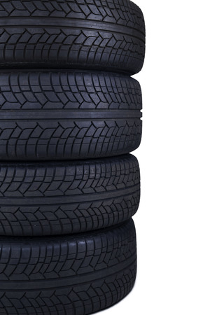Closeup of four tires with black color stacked in the studio, isolated on white background photo