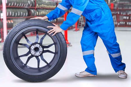 tire service: Male technician with a blue clothes changing a tire in the workshop