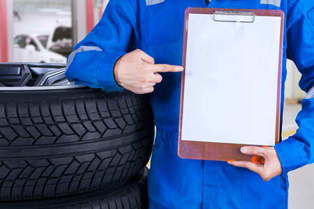 tire repair shop: Mechanic with a blue workwear showing an empty copyspace while standing next to tires