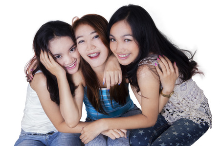 laughing girl: Portrait of beautiful three teenage girls smiling at the camera while embracing to each other