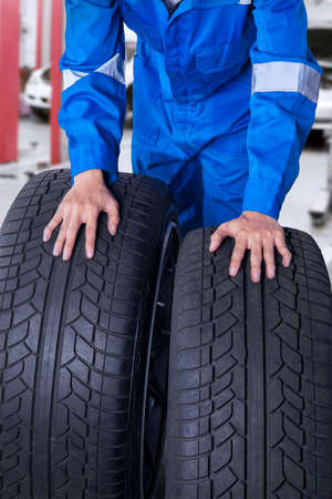 disassembly: Male mechanic with blue workwear holding two textured black tires in the garage Stock Photo