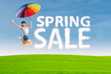 Spring sale clouds and woman with umbrella jumping at meadow photo