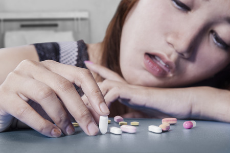 teenager girl: Closeup of female drug addict with stressful expression, choosing pills on the table Stock Photo