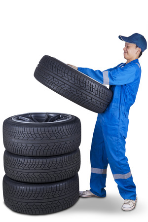 to pile up: Portrait of male technician with a blue uniform and pile up four black tires, isolated on white Stock Photo