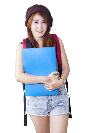 short pants: Portrait of a modern teenage girl student with short pants standing in the studio while carrying bag and folder
