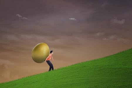 Businessman carry golden egg on steep hill photo