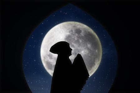 salat: Card design silhouette of female muslimah pray on blue moon