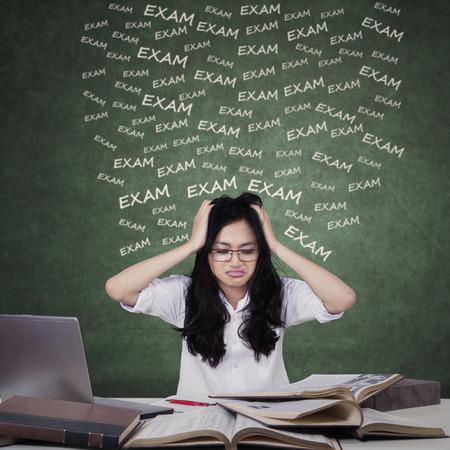 Verwarde tienermeisjes voorbereiding voor examen tijdens de studie met laptop en handboeken