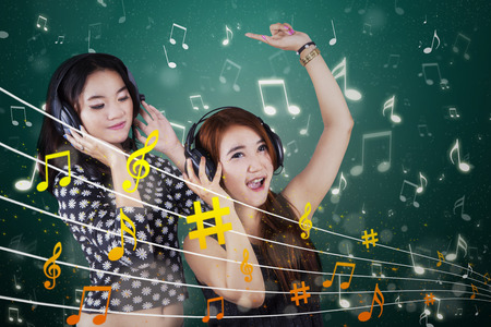 Two beautiful teenage girls using headphones to listen music while singing and dancing together photo