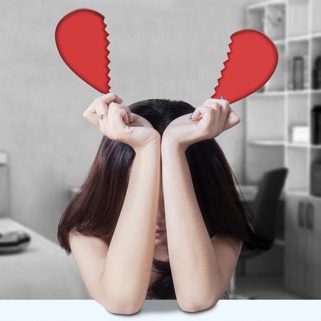 mujeres tristes: Solitaria chica adolescente sentado solo en el dormitorio mientras mantiene el corazón roto Foto de archivo