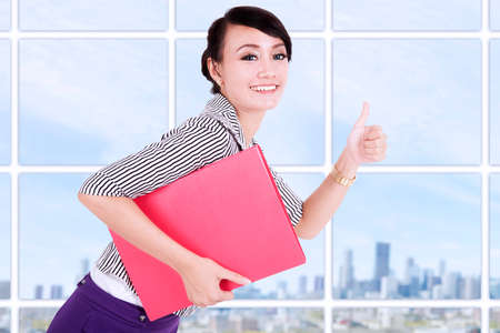 filipino adult: Young businesswoman showing thumb up and holding a folder on modern office Stock Photo