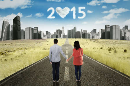 highway love: Back view of young couple standing on the road while holding hands and looking at cloud shaped numbers 2015