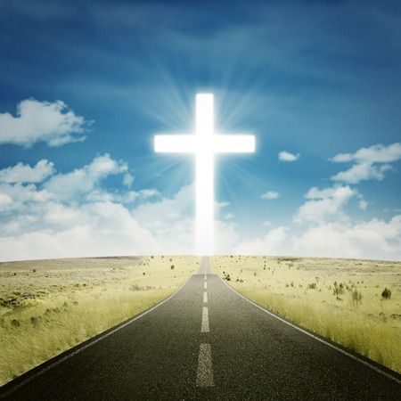 Empty road toward the heaven with a cross on the end of the road Фото со стока