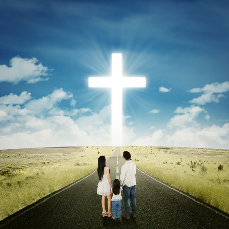 Rear view of family standing on the road with a cross on the end of the road Stock Photo