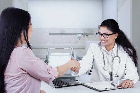 examination room: Portrait of beautiful indian doctor shaking hands to patient in the examination room