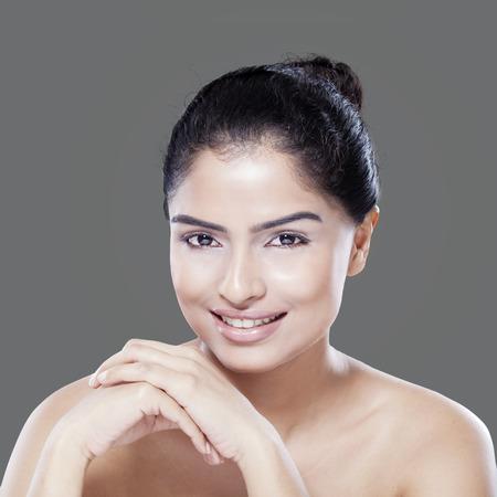 fille indienne: Jeune femme avec une peau saine souriant � la cam�ra, tourn� en studio sur fond gris