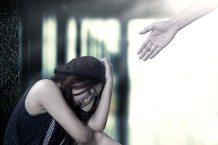 fille triste: Portrait de stressant adolescente assis sur le sol avec une main sortant de fond lumineux offre de l'aide Banque d'images