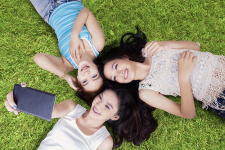 asian hair: Unique perspective of beautiful teenage girls lying down on grass while taking self portrait with cellphone at field
