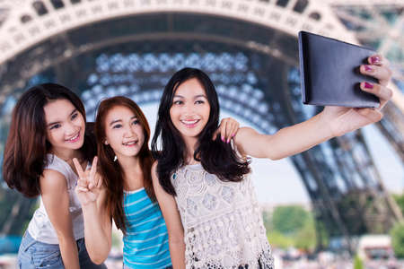 fille indienne: Trois jolies filles adolescentes en utilisant un t�l�phone mobile de prendre l'auto image � la Tour Eiffel