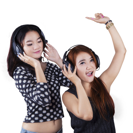 Portrait of two beautiful teenage girls dancing while listening music with headphones, isolated over white photo