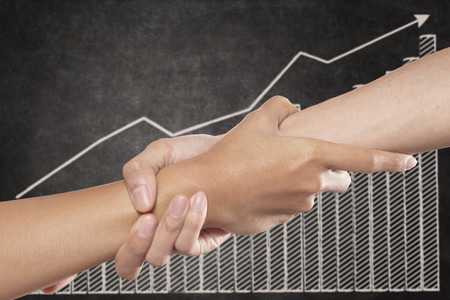 growing partnership: A helping hand with profit growth chart Stock Photo