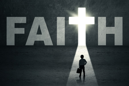 mystery of faith: Little kid standing in front of faith door with bright light Stock Photo